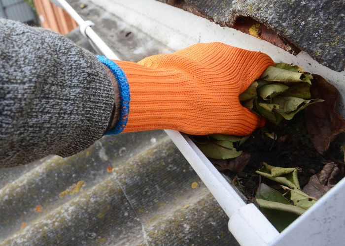 Removing debris from gutters and bagging it up by hand.