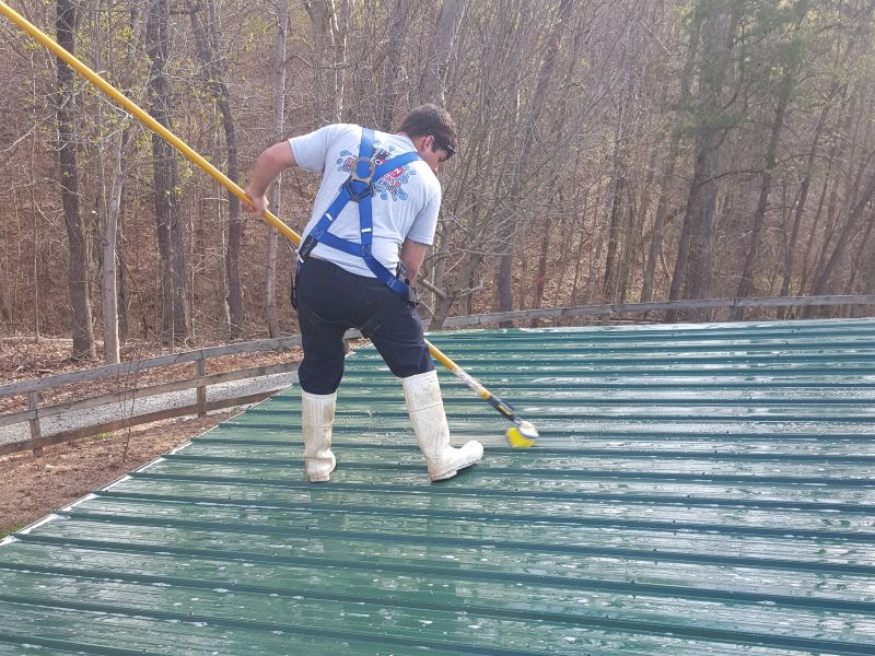 Scrubbing a metal roof to remove oxidation.