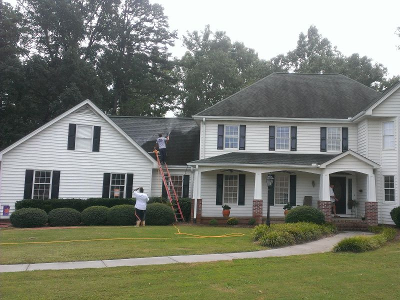A huge house getting black streaks removed from their roof.