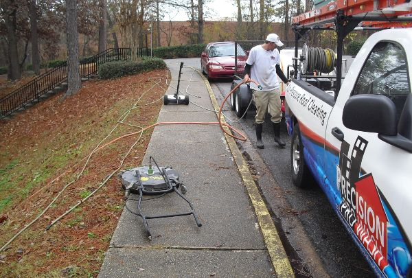 Setting up the pressure washer on a commercial concrete cleaning job.