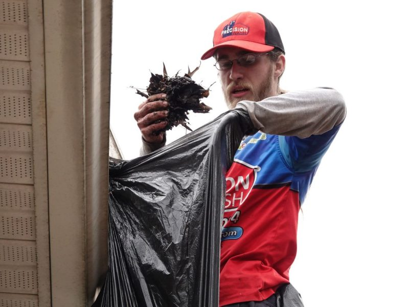 Our star technician cleaning and bagging debris from a gutter system.